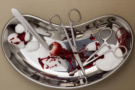 ojo humano: Instrumentos quirúrgicos con un ojo humano a distancia. Foto de archivo