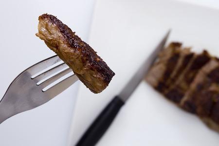 Piece of medium rare steak on a fork. Stock Photo