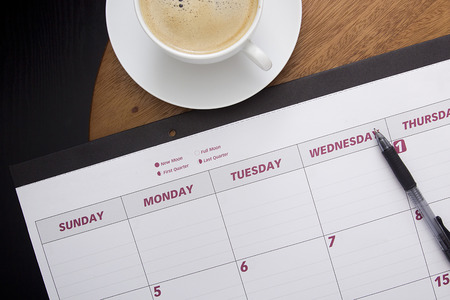 schedulers: Office calendar planner on the coffee table with a cup of coffee. Stock Photo