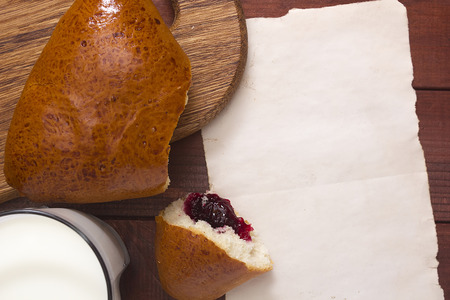 informational: Roll with jam on a kitchen cutting board, a glass of milk and paper for informational message.