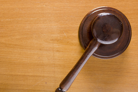 legislator: Hammer used in court on a wooden tabletop.