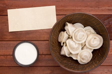 sour cream: Dumplings in a ceramic dish with sour cream sauce. Stock Photo