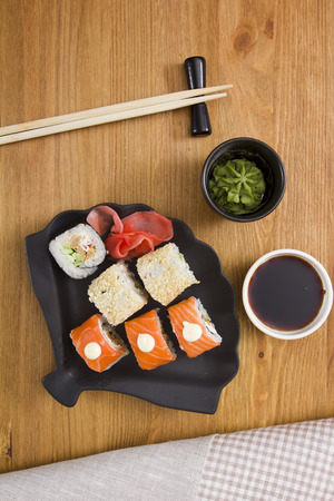 Set of sushi and rolls with mustard greens and Ginger, wasabi, wooden sticks.