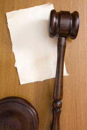 magistrate: Judges wooden gavel against a background paper for the information of the message.