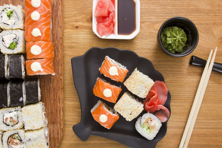 Big set of sushi and rolls with mustard greens and Ginger, wasabi, wooden sticks. Stock Photo