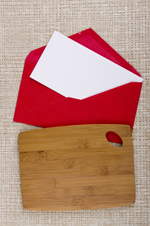 Wooden cutting board and red paper envelope with a letter.