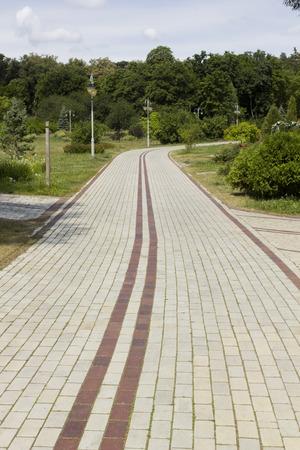 暗い茶色の分周器と白いレンガが並ぶ公園の路地。