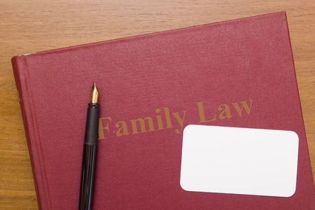 family law: Family law - book and fountain pen with a clean business card.