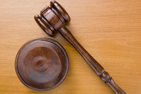legislator: Hammer used in court on a wooden tabletop.