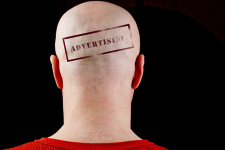 receded: Stamp imprint on his bald head man Advertising. Stock Photo