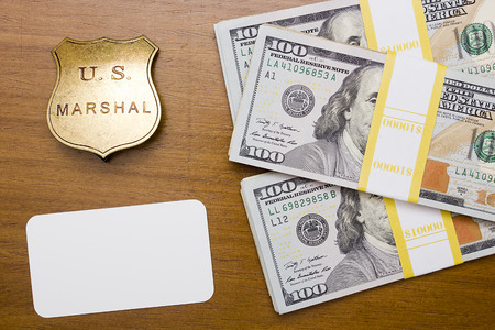 marshal: Sign of the US prison staff - marshal sign with packs of dollars.