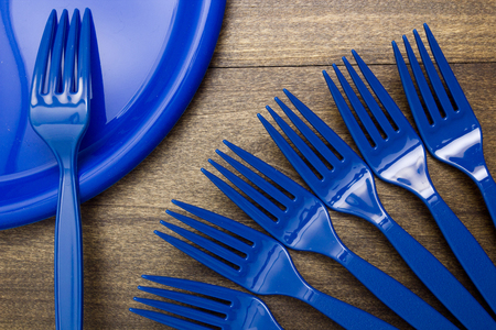 plate setting: Plastic disposable forks and plates for going on a picnic. Stock Photo