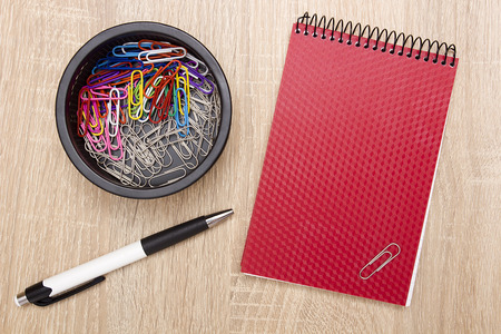 Office notebook and office paper clips on the desk. 免版税图像