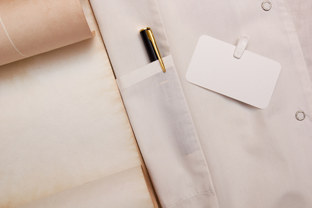 White gown with a pen in his pocket.