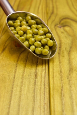 canned peas: Green canned peas in a steel spoon weighed.