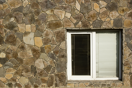 wall covering: Modern plastic window with horizontal blinds and stone wall covering, exterior.