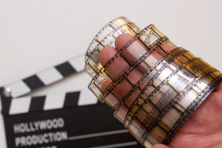 film industry: Old film strip in the mans hand as a symbol of cinema. Stock Photo