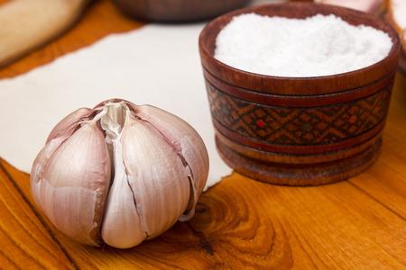 bulbet: Garlic head and salt in a wooden salt shaker.