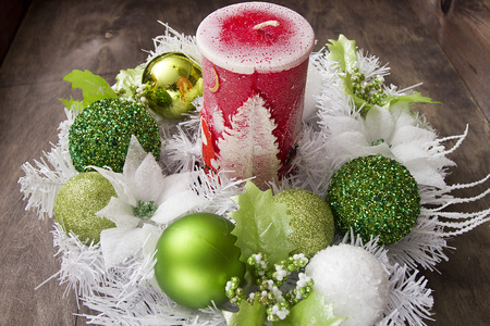 Big New Year candle and festive wreath of white and green balls.