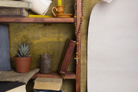 canonical: Shelf with old religious books, candles and canonical cross.