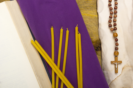 tomes: Thin candles on purple cloth used in religion and ancient tomes. Stock Photo
