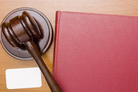 Houten hamer van de wet, met een boek in een rode kaft.