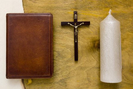 crucified: Catholic Bible bound in leather and crucified on a wooden cross.