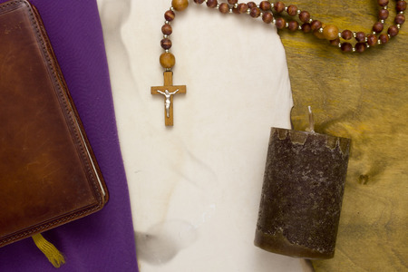 A small wooden catholic cross on a wooden chain. Stock Photo