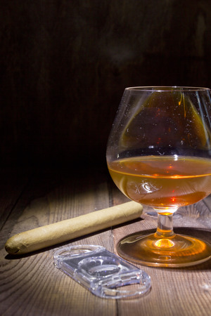 drunks: Cognac in glass and cigar on a wooden surface Stock Photo