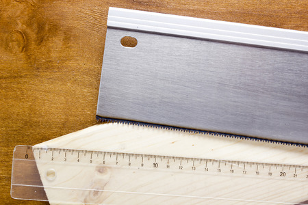 Toothed steel hand saw cutting through a new boards  of wood left in position surrounded by wood chips with nobody in the frame in a DIY, carpentry, woodworking or joinery concept 版權商用圖片