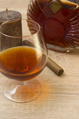 cognac: Cognac in glass and cigar on a wooden surface Stock Photo