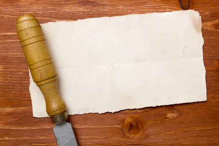 special steel: Rasp with wooden handle on a piece of paper on a wooden background