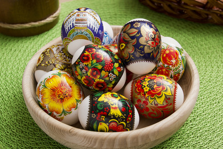 eastertime: Easter eggs in a wooden plate on a green background Stock Photo