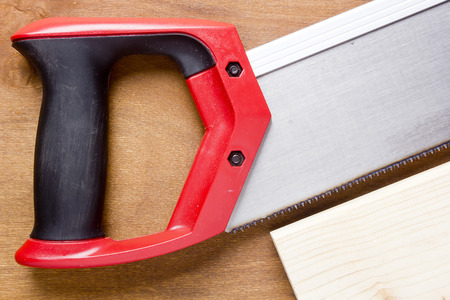 cutting through: Toothed steel hand saw cutting through a new boards  of wood left in position surrounded by wood chips with nobody in the frame in a DIY, carpentry, woodworking or joinery concept Stock Photo