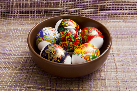 eastertime: Easter eggs in an earthenware plate on a purple background