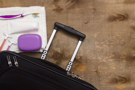 Suitcase traveler, toiletries on a wooden background.
