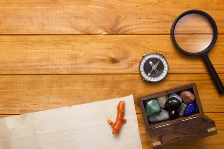 pietre preziose: Colorate pietre semi preziose, lente di ingrandimento su uno sfondo di legno