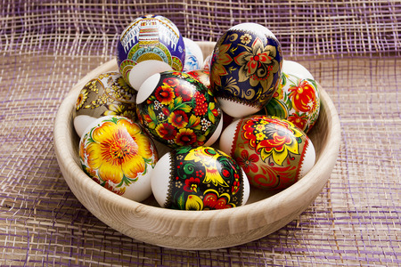 eastertime: Easter eggs in a wooden plate on a purple background