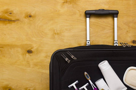 productos de aseo: viajero maleta, artículos de higiene personal sobre un fondo de madera. Foto de archivo
