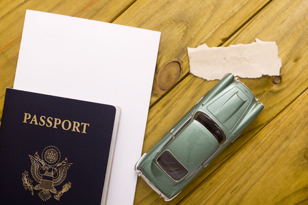 Passport travel with car model on a wooden background