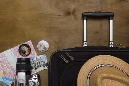 Traveller's koffer met apparatuur met camera op een houten achtergrond