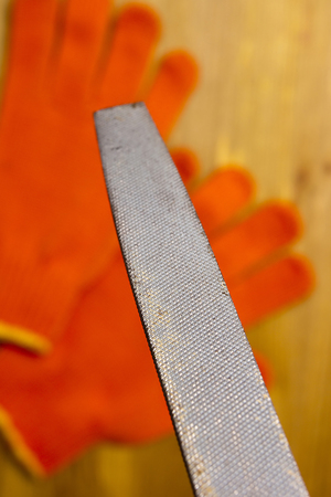 industrious: Files and work gloves on a wooden table available to work Stock Photo