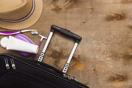 Koffer reiziger, toiletartikelen en een hoed op een houten achtergrond.