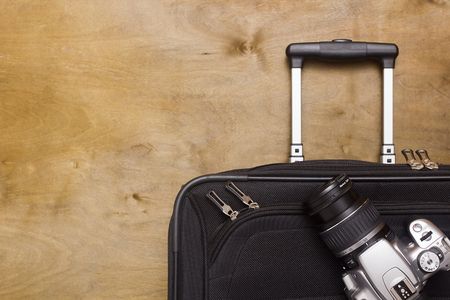Traveler's suitcase with  equipment with camera on a wooden background