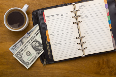 laundered: Open daily, money and cup of coffee on a wooden background Editorial