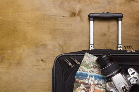 Traveler's suitcase with  equipment with camera and old pictures on a wooden background