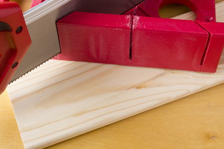 マイター ボックスを使用してボードを切り取って、木製の背景で見た