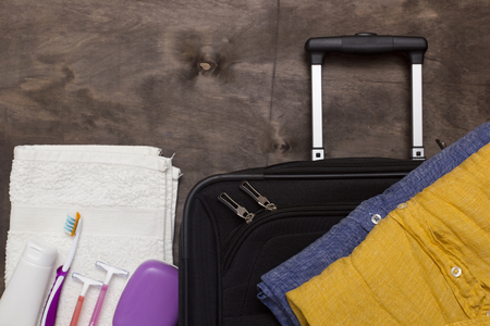 productos de aseo: Suitcase traveler, toiletries on a wooden background.