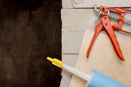caulk: Metal Building Contractors Caulking Gun Tool on a stone background