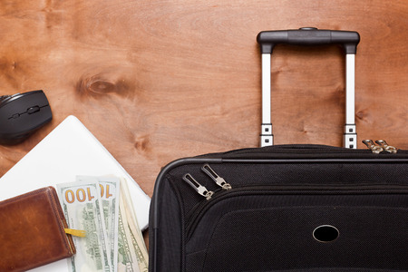 Schwarzer Koffer und Gepäck für eine Geschäftsreise auf einem hölzernen Hintergrund